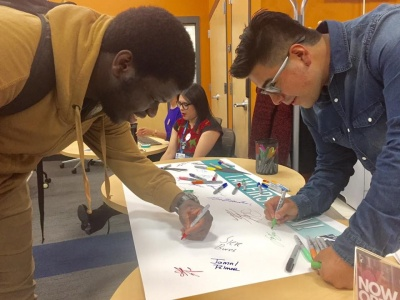 First gen students signing the pledge banner